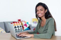 Studentessa di risata che impara a casa con il computer portatile Fotografie Stock