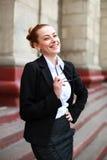 Studentessa di risata in vestito davanti all'università Immagine Stock