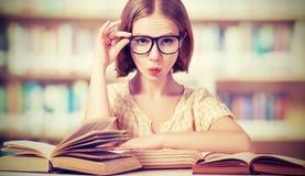 Studentessa divertente con i libri di lettura di vetro Immagine Stock
