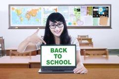 Studentessa e un testo di nuovo alla scuola Immagini Stock