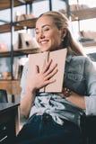 Studentessa emozionante che abbraccia libro in biblioteca Fotografie Stock