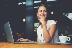 Studentessa felice affascinante che per mezzo del computer portatile per preparare per il lavoro di corso Fotografia Stock