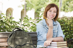 Studentessa felice On Campus con lo zaino sul banco Immagine Stock Libera da Diritti