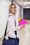 Studentessa felice che cammina nel corridoio Fotografie Stock