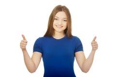 Studentessa felice che mostra i pollici su Immagini Stock Libere da Diritti