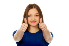 Studentessa felice che mostra i pollici su Fotografia Stock