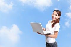 Studentessa felice che per mezzo del computer Immagini Stock