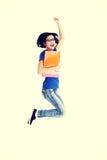 Studentessa felice che salta con un taccuino Fotografia Stock