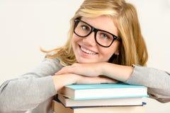 Studentessa felice con la pila di libri Immagini Stock