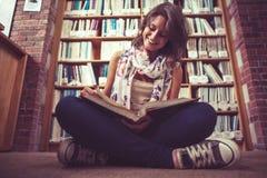 Studentessa felice contro lo scaffale per libri che legge un libro sul pavimento delle biblioteche Fotografie Stock Libere da Diritti