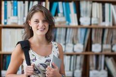 Studentessa felice contro lo scaffale per libri con il PC della compressa e borsa in biblioteca immagini stock libere da diritti