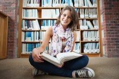 Studentessa felice contro lo scaffale per libri con un libro sul pavimento delle biblioteche Immagine Stock Libera da Diritti