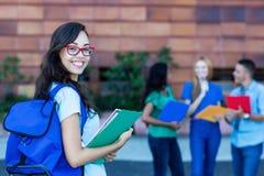 Studentessa francese nerd felice con il gruppo di studenti immagini stock