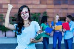 Studentessa francese nerd incoraggiante con il gruppo di studenti immagini stock