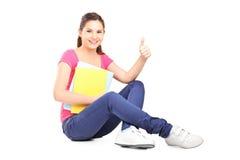 Studentessa giovane che si siede sul pavimento e che dà pollice su Fotografia Stock