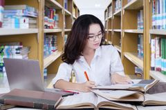 Studentessa graziosa che fa compito scolastico in biblioteca Fotografia Stock