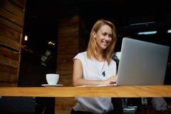 Studentessa graziosa con introduzione sveglia di sorriso qualcosa sul NET-libro mentre rilassandosi dopo le conferenze in univers Fotografia Stock