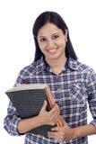 Studentessa indiana sorridente contro bianco Immagine Stock