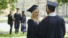 Studentessa laureata che parla con laureato del maschio, cappello commovente, amici felici video d archivio