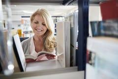 Studentessa matura Browsing Through Books in biblioteca immagini stock libere da diritti