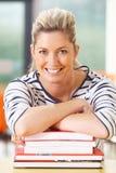 Studentessa matura Studying In Classroom con i libri Immagine Stock