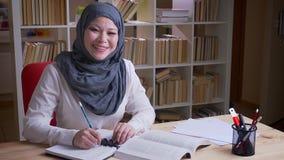 Studentessa musulmana adulta del portraitof del primo piano nel hijab che studia per un esame medico che legge un libro e che pre video d archivio