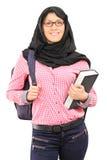 Studentessa musulmana con lo zaino che tiene un libro Fotografia Stock