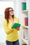Studentessa in occhiali con il manuale Immagini Stock