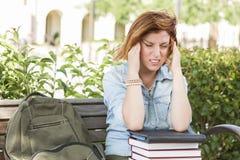 Studentessa Outside con l'emicrania che si siede con i libri e la parte posteriore Immagine Stock