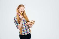 Studentessa pensierosa che sta con i libri Immagine Stock