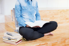 Studentessa premurosa che si siede lettura seria un libro in un Li Fotografia Stock Libera da Diritti