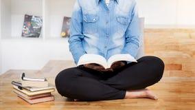Studentessa premurosa che si siede lettura seria un libro in un Li Immagini Stock Libere da Diritti