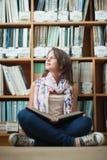 Studentessa premurosa contro lo scaffale per libri con un libro sul pavimento delle biblioteche Fotografia Stock
