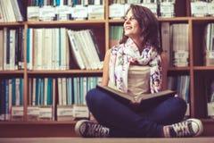 Studentessa premurosa contro lo scaffale per libri sul pavimento delle biblioteche Immagine Stock