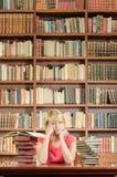 Studentessa preoccupata con i gomiti sulla tavola delle biblioteche Immagine Stock Libera da Diritti