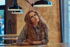 Studentessa riccia della giovane testarossa astuta che si siede ad una tavola nella mensa dell'istituto universitario durante una Fotografie Stock Libere da Diritti