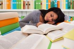 Studentessa Sleeping On Books in biblioteca Immagini Stock Libere da Diritti