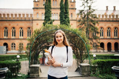 Studentessa sorridente all'aperto con la borsa ed il taccuino vicino all'università Immagini Stock