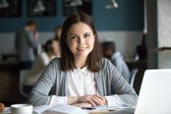 Studentessa sorridente che esamina macchina fotografica che si siede alla tavola del caffè Fotografie Stock