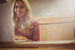 Studentessa sorridente che per mezzo del computer portatile Fotografia Stock Libera da Diritti