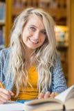 Studentessa sorridente che si siede allo scrittorio delle biblioteche Fotografie Stock