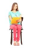 Studentessa sorridente che si siede su una sedia e sulla scrittura delle note Immagine Stock