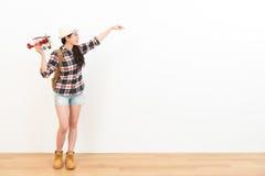 Studentessa sorridente che sta sul pavimento di legno Immagini Stock