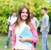 Studentessa sorridente che tiene un libro al parco Fotografie Stock