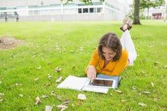Studentessa sorridente che utilizza il PC della compressa nel prato inglese Fotografia Stock Libera da Diritti
