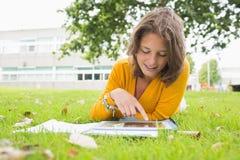 Studentessa sorridente che utilizza il PC della compressa nel prato inglese Immagini Stock Libere da Diritti