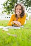 Studentessa sorridente che utilizza il PC della compressa nel prato inglese Fotografie Stock