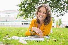 Studentessa sorridente che utilizza il PC della compressa nel prato inglese Fotografia Stock