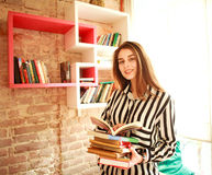 Studentessa sorridente con i libri in biblioteca Fotografie Stock