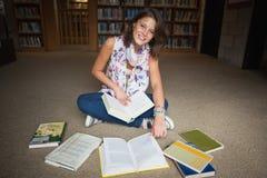 Studentessa sorridente con i libri sul pavimento delle biblioteche Fotografia Stock